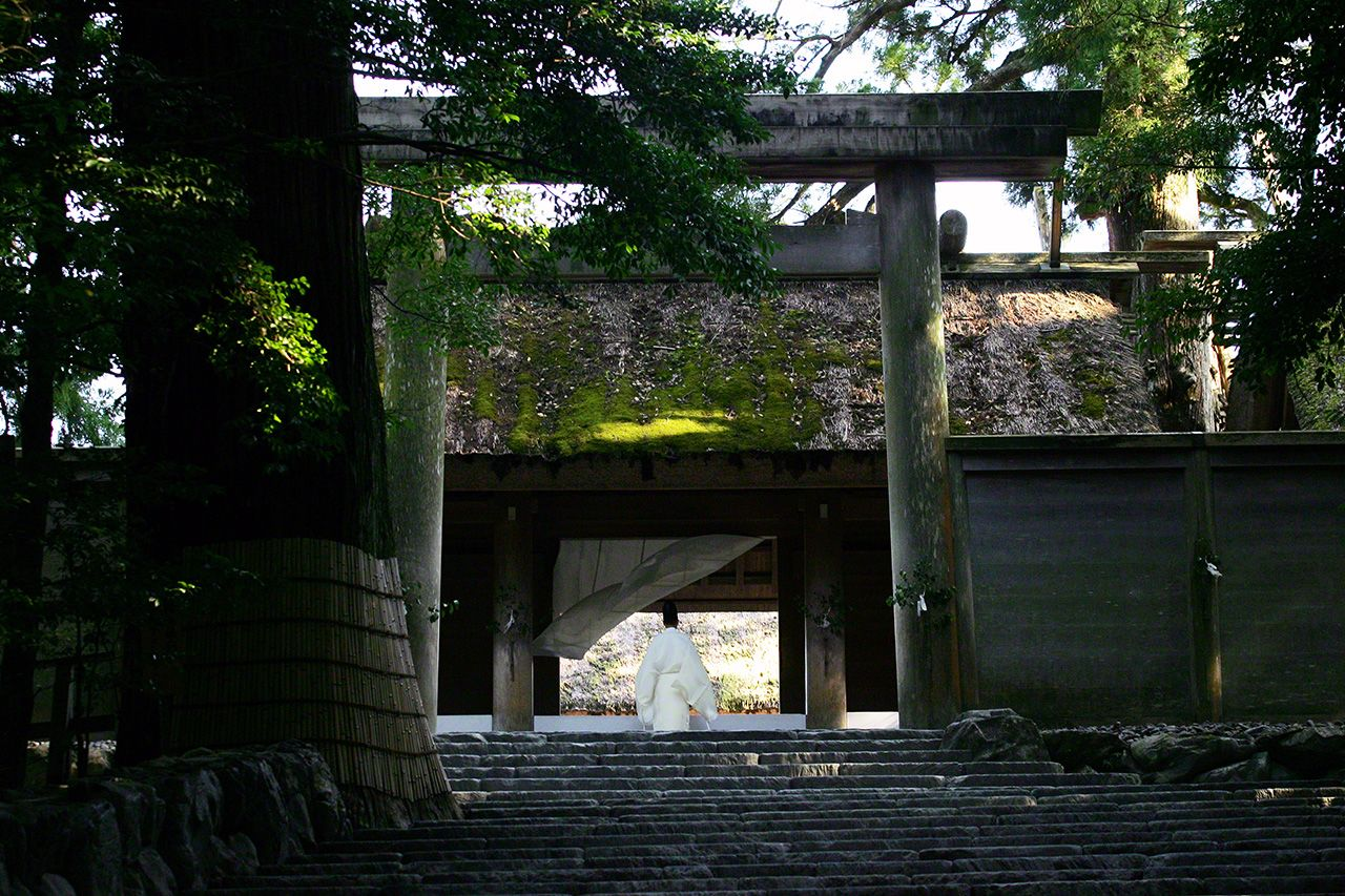 July 1<br>A curtain hung across the shrine entrance is blown back by a gust of wind as a priest approaches.