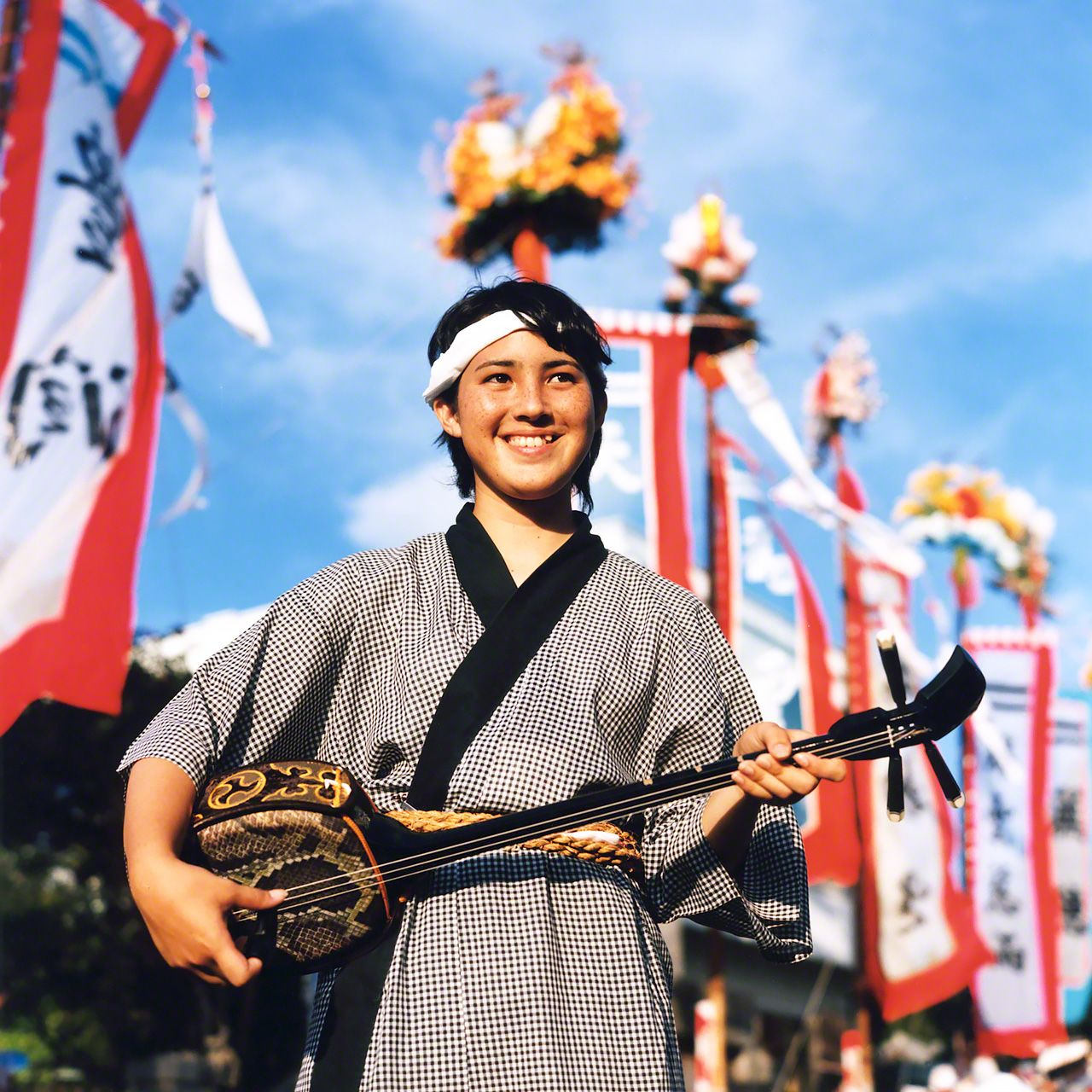 A high school girl holding a \sanshin\ at an Ishigakijima harvest festival.