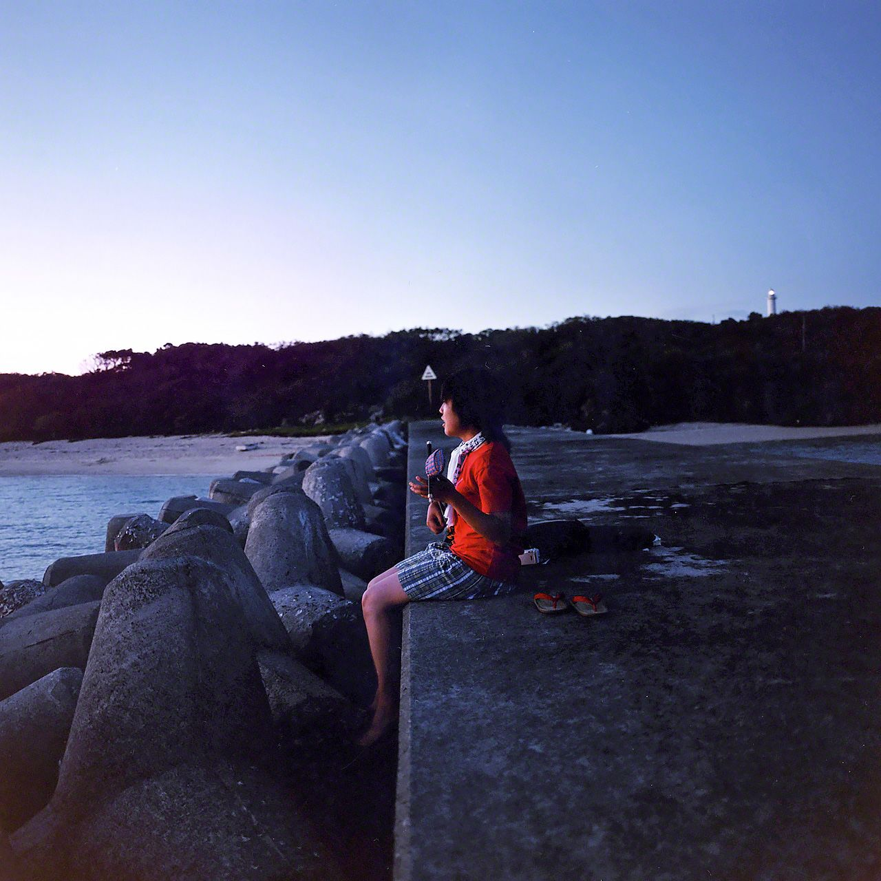 A girl practices the \sanshin\ beside the sea on Hatomajima.