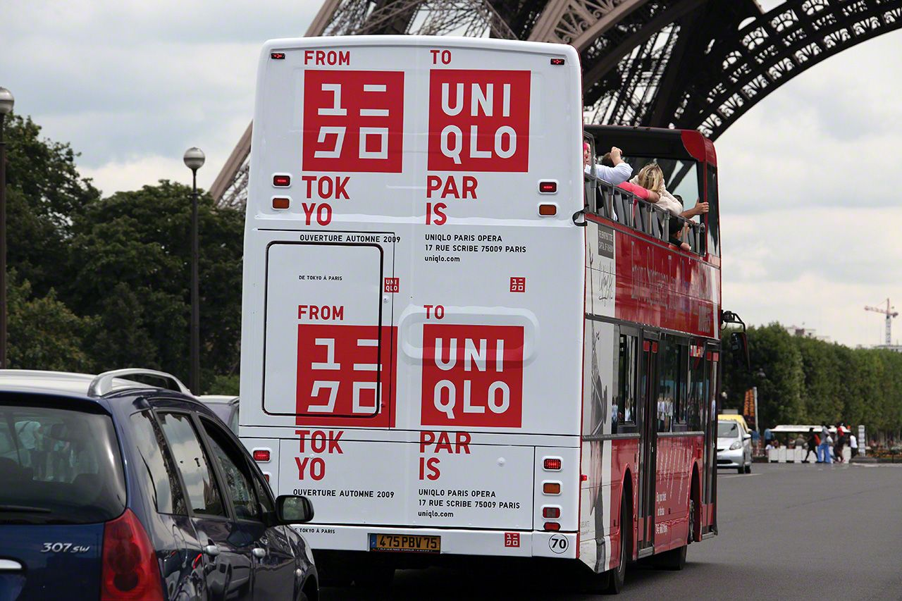 A double-decker tour bus bearing the Uniqlo logo passes beneath the Eiffel Tower.