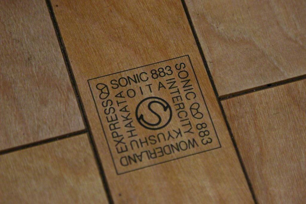 A Sonic logo mark incorporated unobtrusively into the wooden floor of the train.