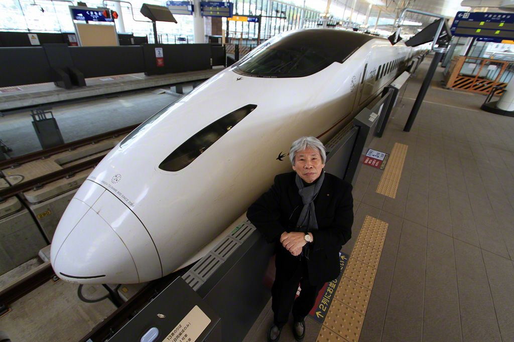 Mitooka Eiji stands next to a stationary Kyūshū Shinkansen train. Although the basic body of the train is the same as that used on the Tōkaidō and Sanyō Shinkansen, Mitooka's innovative design makes it feel like a totally different train.