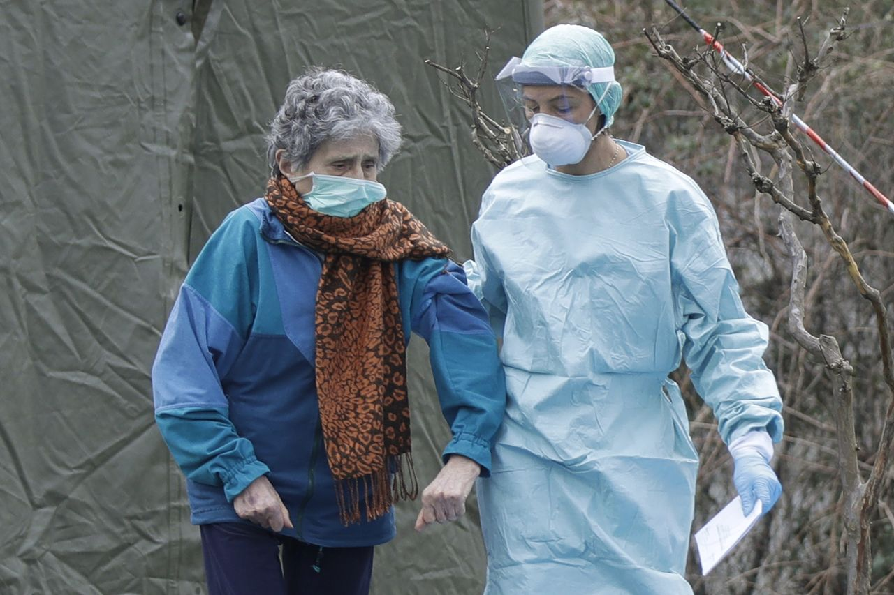 An elderly patient assisted by a doctor at a medical facility in Brescia in the northern Italian region of Lombardy. As of March 12, there were 15,113 cases of novel coronavirus in Italy and 1,016 deaths. Italy is the second country after China, where the virus first appeared, to have a death toll that exceeds 1,000. (© Luca Bruno/AP Photo/Aflo)