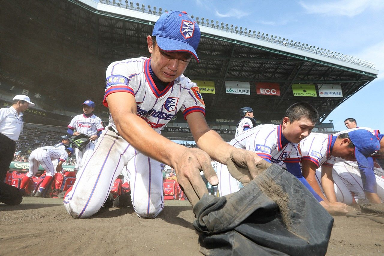 Players from Shimonoseki Kokusai High School collect infield dirt after losing in the quarterfinals to Nichi-Dai San in August 2018. (© Jiji)