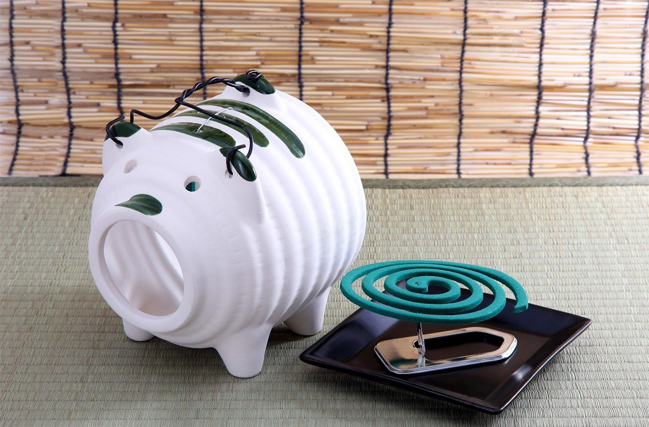 A mosquito coil and traditional pig-shaped holder.