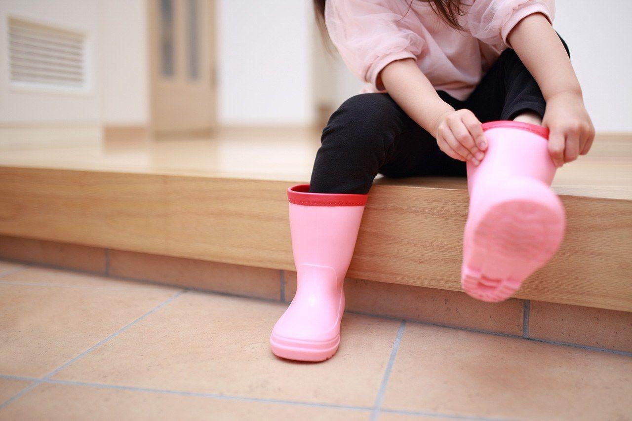 Melepas sepatu bot, sambil duduk di anak tangga agarimachi, yang memisahkan tingkat tataki dari rumah utama. (© Pixta)
