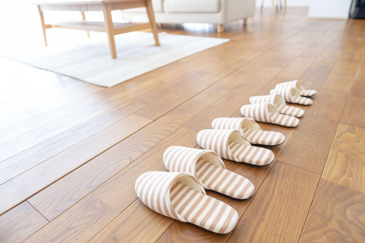 Sandal bergaris siap digunakan di rumah modern berlantai kayu. (© Pixta)