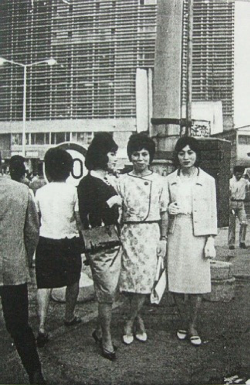 Members of the secret cross-dressing club Fuki posing for a photo in front of the refurbished Shinjuku Station building in June 1964.