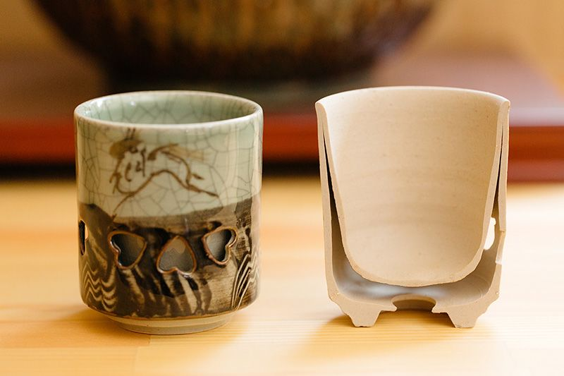 A double-layered tea cup and a cross-section of it. The heart-shaped holes are called nami-chidori, or zigzagging plovers, and can represent a couple forging through heavy waves together. They are a symbol of conjugal harmony and the achievement of shared goals.