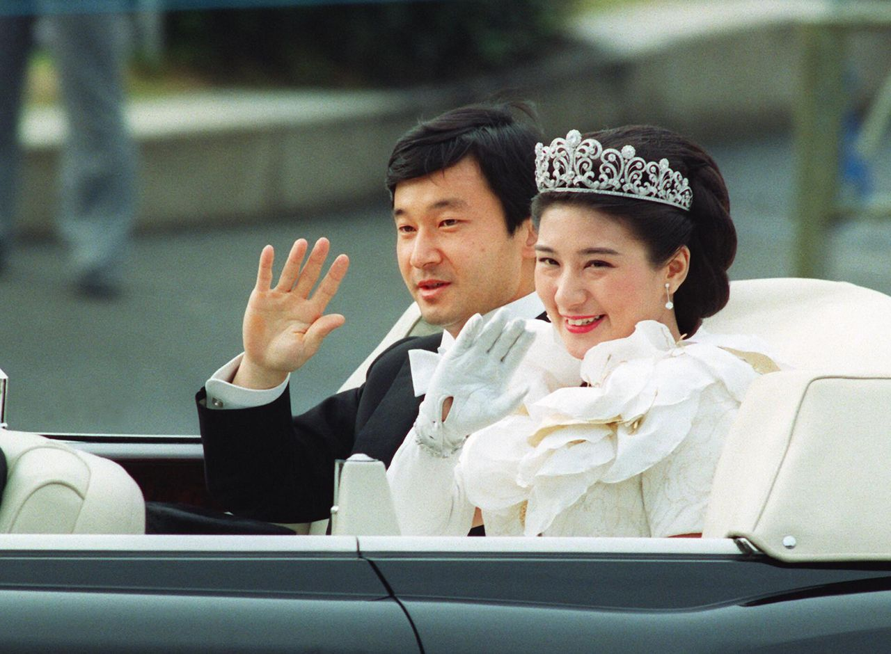 Crown Prince Naruhito and Crown Princess Masako wave to the crowds during their wedding parade in Tokyo in June 1993. (© Jiji)