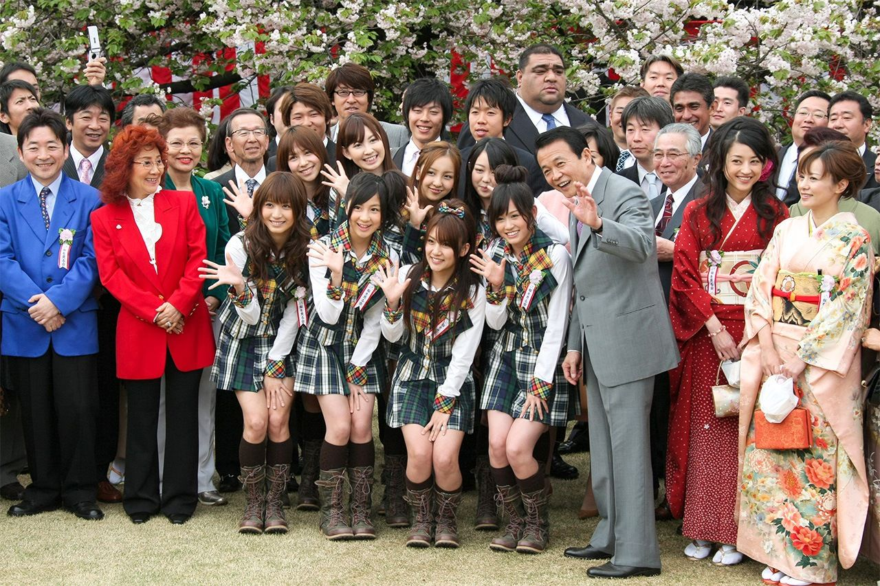 AKB48 members, in uniforms at center, pose for a photo with then Prime Minister Asō Tarō at a cherry blossom viewing party in Tokyo on April 18, 2009. (©Jiji)