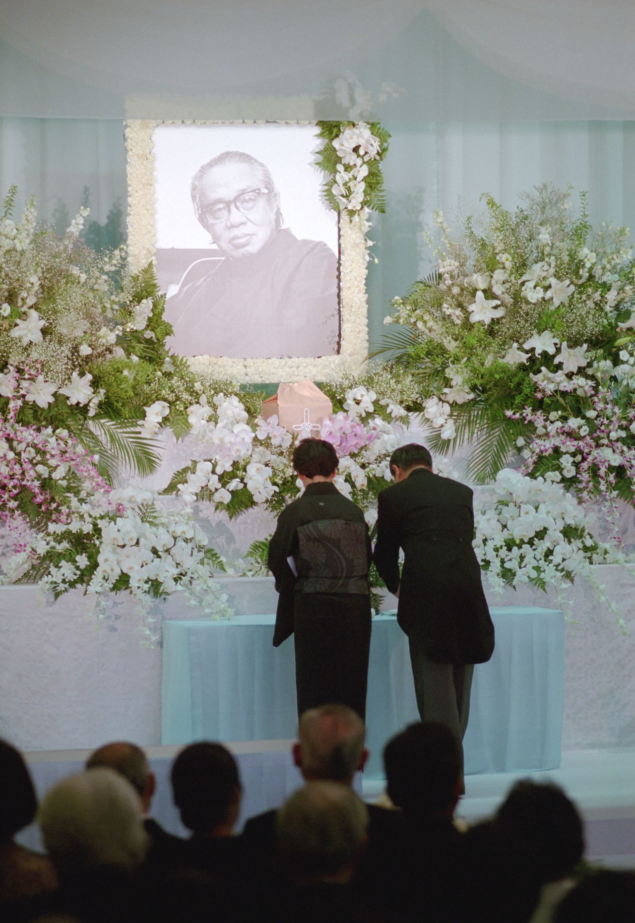Matsumoto's eldest son Yōichi and his wife offer flowers at Matsumoto's memorial service, held on August 10, 1992. (© Jiji)