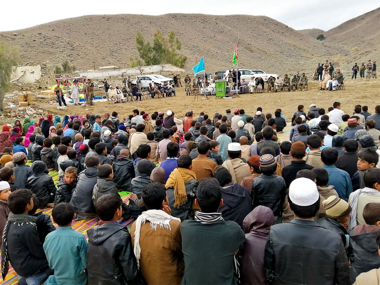 People gather for a ceremony to mark the reopening of the local school in March 2019. Army representatives can be seen to the right of the flagpole. (Photo courtesy Japanese Organization for International Cooperation in Family Planning)