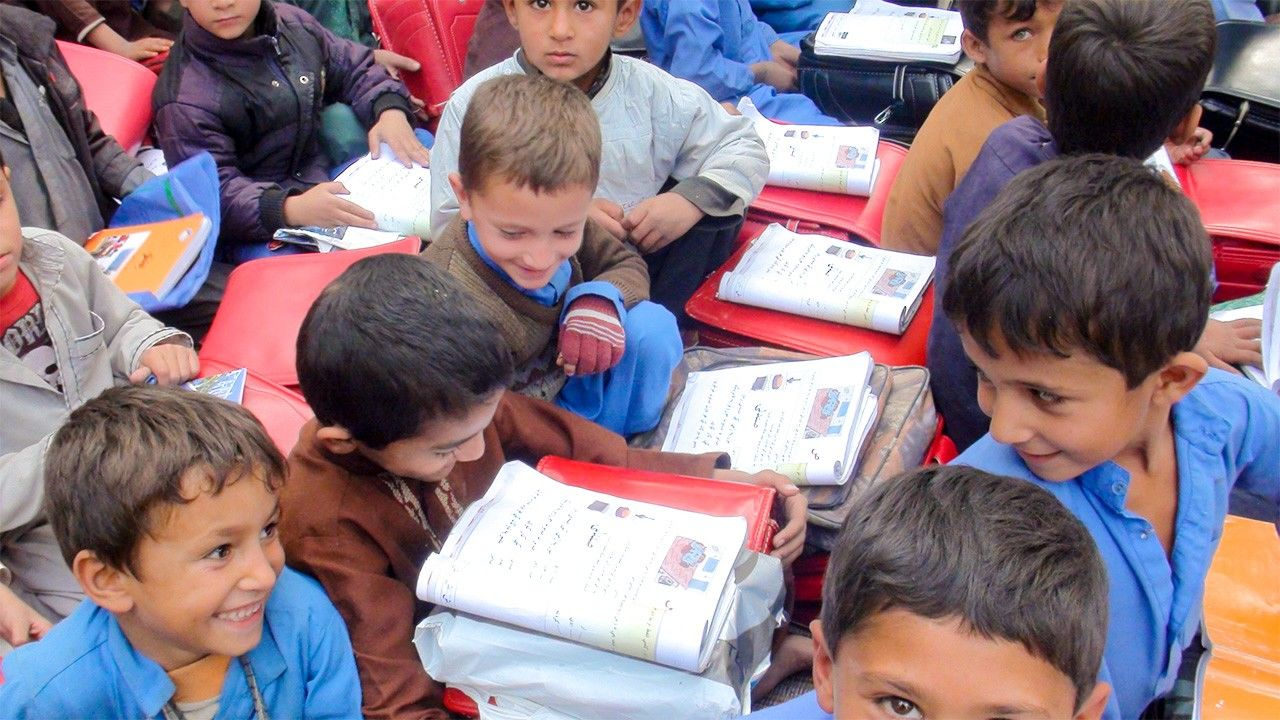 Children in Afghanistan use their backpacks as impromptu desks. (Photo courtesy Japanese Organization for International Cooperation in Family Planning)