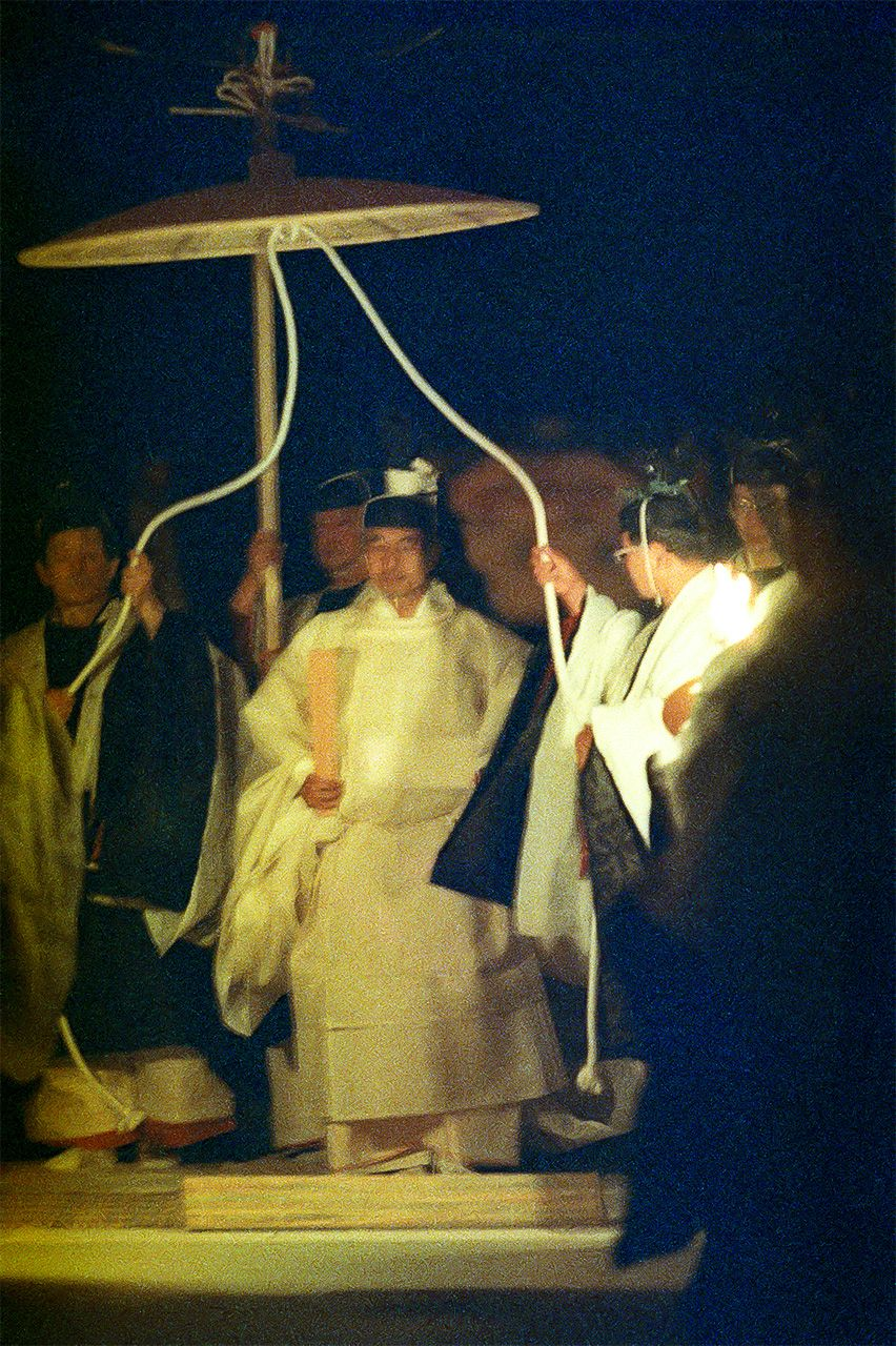 Emperor Akihito accompanied by retainers holding over his head a kasa umbrella-like canopy decorated with a phoenix motif, in the Daijōkyū, Imperial Palace East Gardens, on November 23, 1990. (© Jiji.)