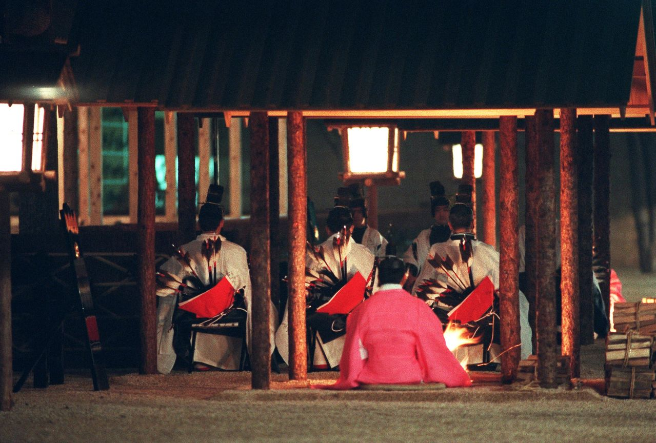 An attendant lights fires at the Sukiden during the 1990 ceremony. (© Jiji)