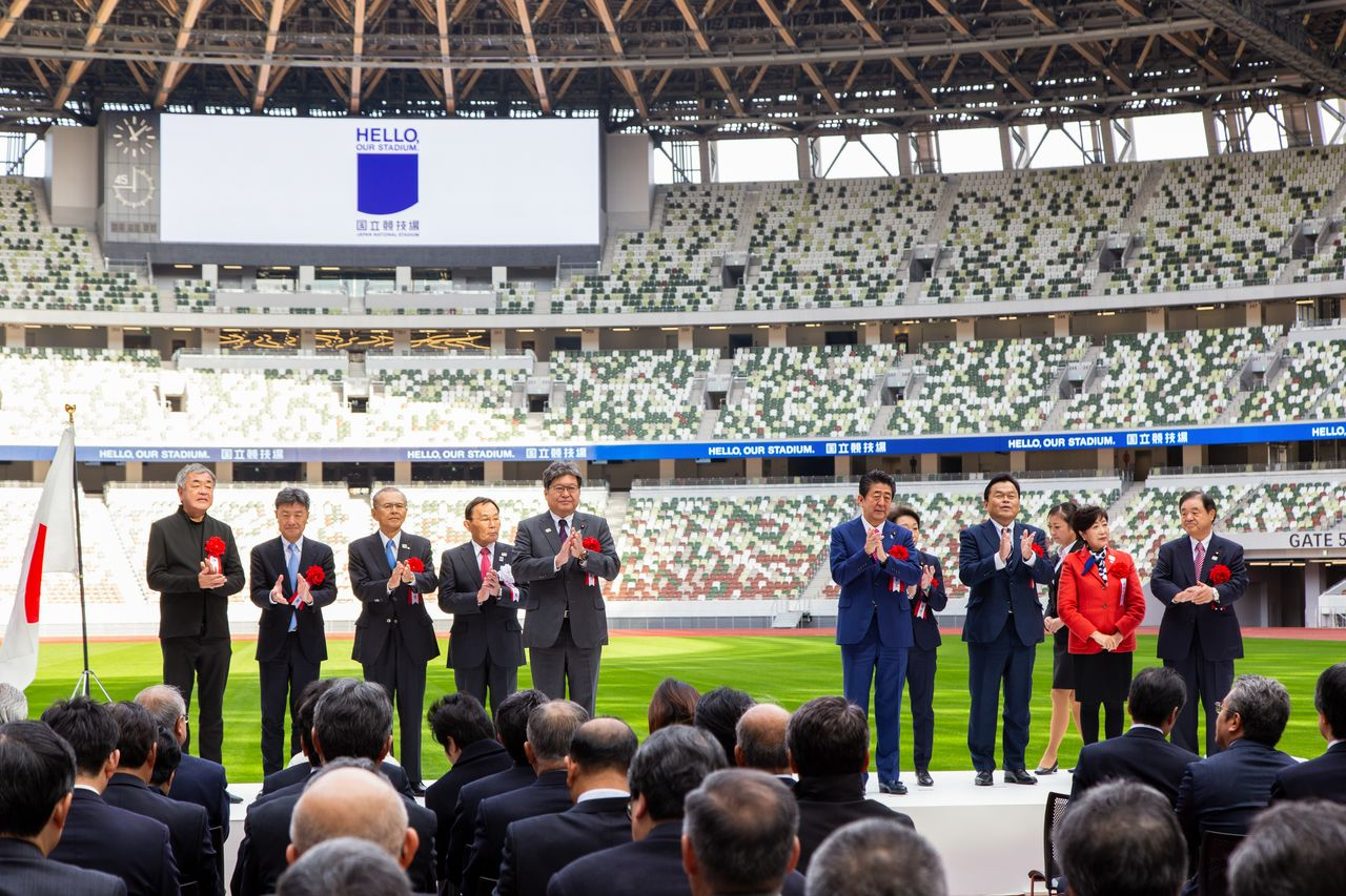 The ceremony to mark the completion of the stadium was attended by Prime Minister Abe Shinzō, Olympic Minister Hashimoto Seiko, and Tokyo Governor Koike Yuriko. At left is architect Kuma Kengo.