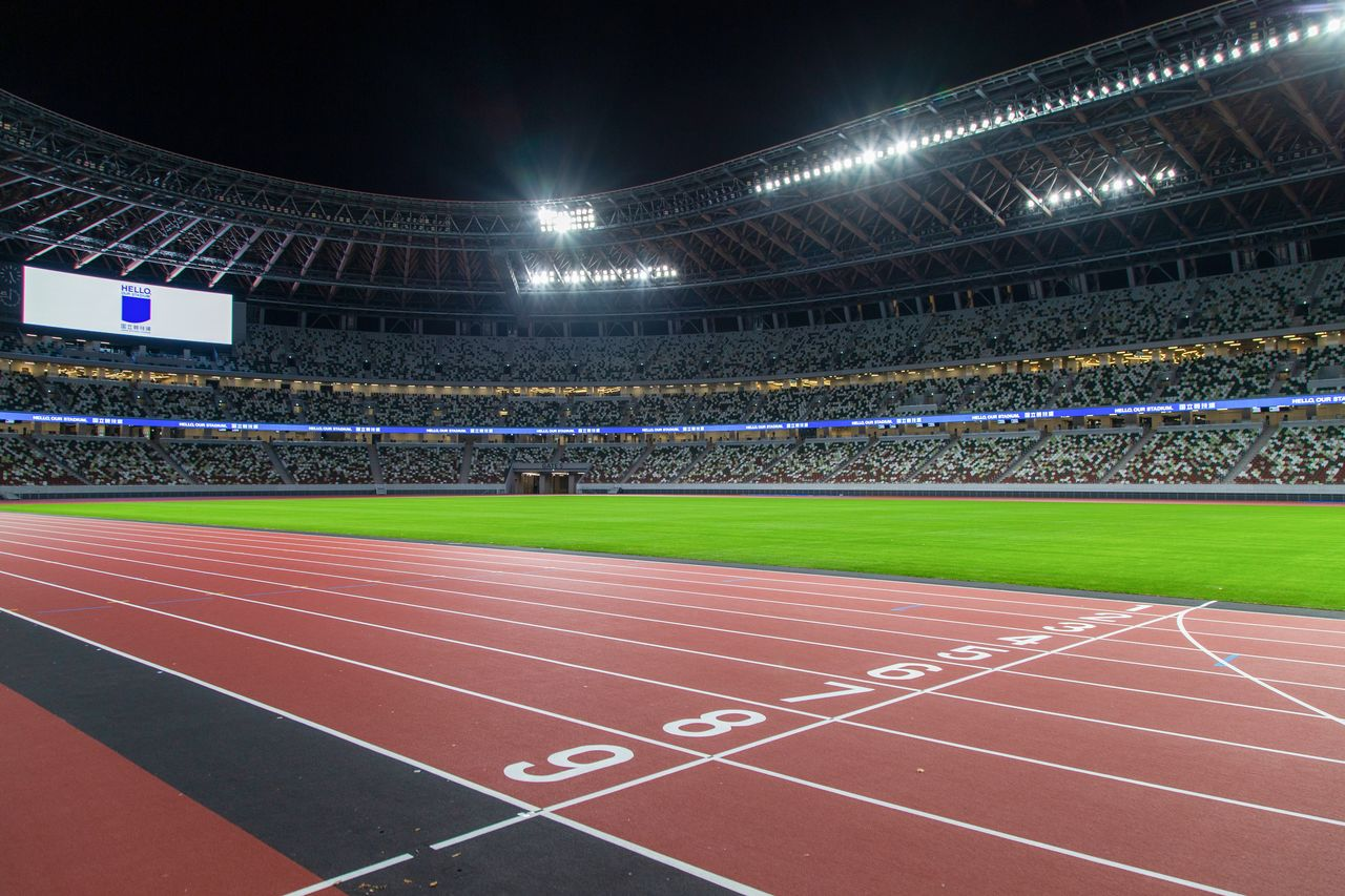 The track, field, and stands under lights.