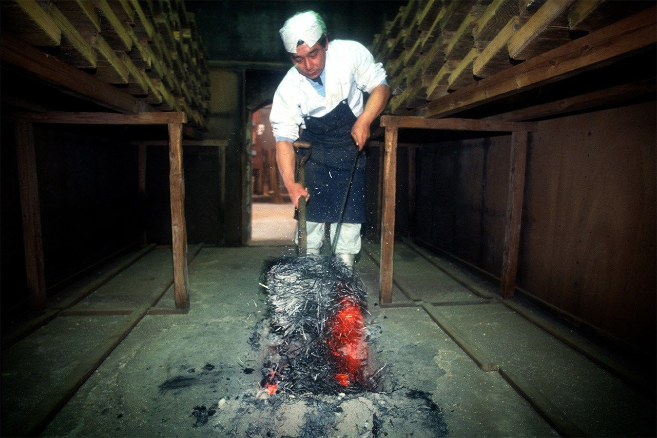 A worker covers glowing embers with straw ash to heat the kōji-muro.