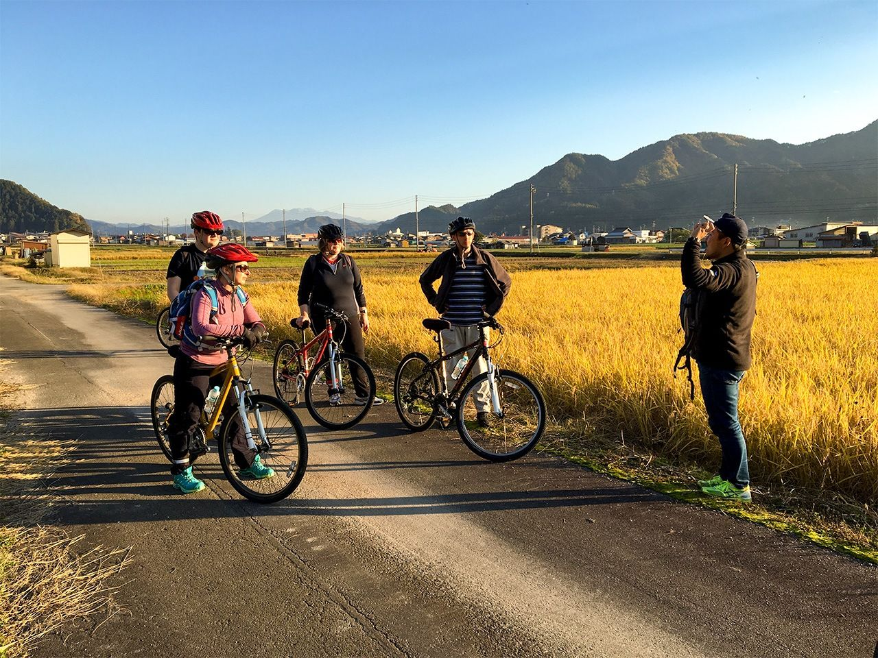 The cyclists dismount on a track between fields for more insights from the guide. (© Demachi Yuzuru)