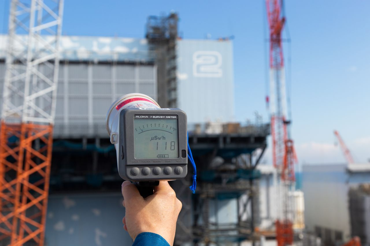 A dosimeter reads 118 microsieverts per hour in an area near the damaged reactor buildings. Although cleanup efforts have lowered radiation levels, the contaminated debris that remains is still a concern for workers.