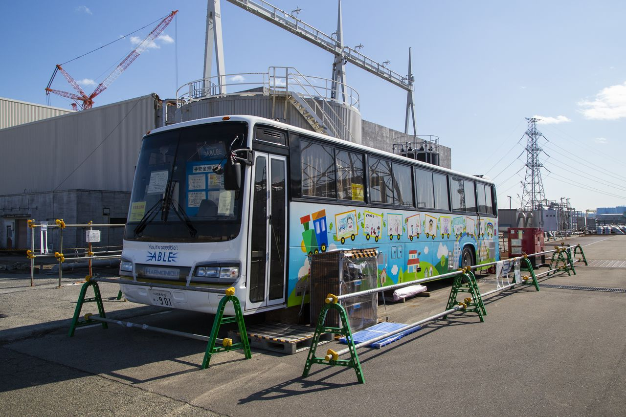 A bus serves as a control room for workers guiding equipment by remote control in areas where radiation remains high. The pictures on the side of the vehicle were drawn by the children of employees who work onsite.