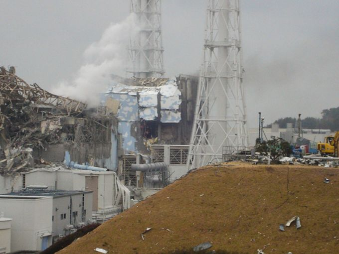 Steam billows from the mangled remains of the Unit 3 (left) and Unit 4 buildings at Fukushima Daiichi on March 15, 2011, following hydrogen explosions. (Photo courtesy Tokyo Electric Power Company Holdings)