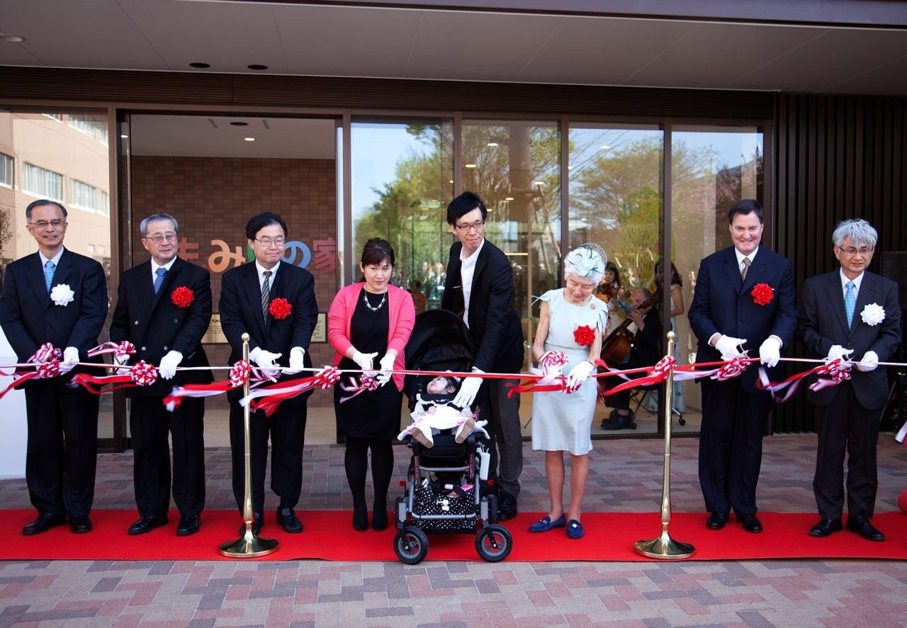 Founder Kidani Masayo (third from right) and managing organization NCCHD Chief Executive Officer Igarashi Takashi (far left) at the ribbon-cutting ceremony for the opening of the newly built Momiji House in 2016. (Photo courtesy of KidsFam Foundation)
