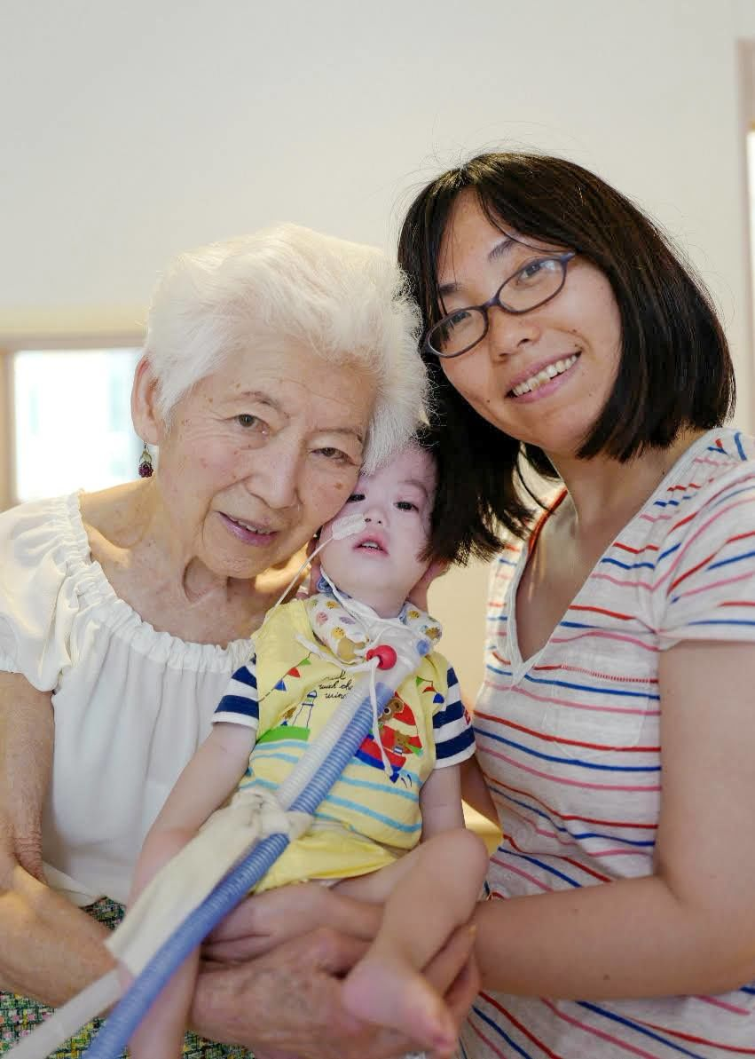 Kidani, at left, with a mother and child staying at Momiji House. (Photo courtesy of KidsFam Foundation)