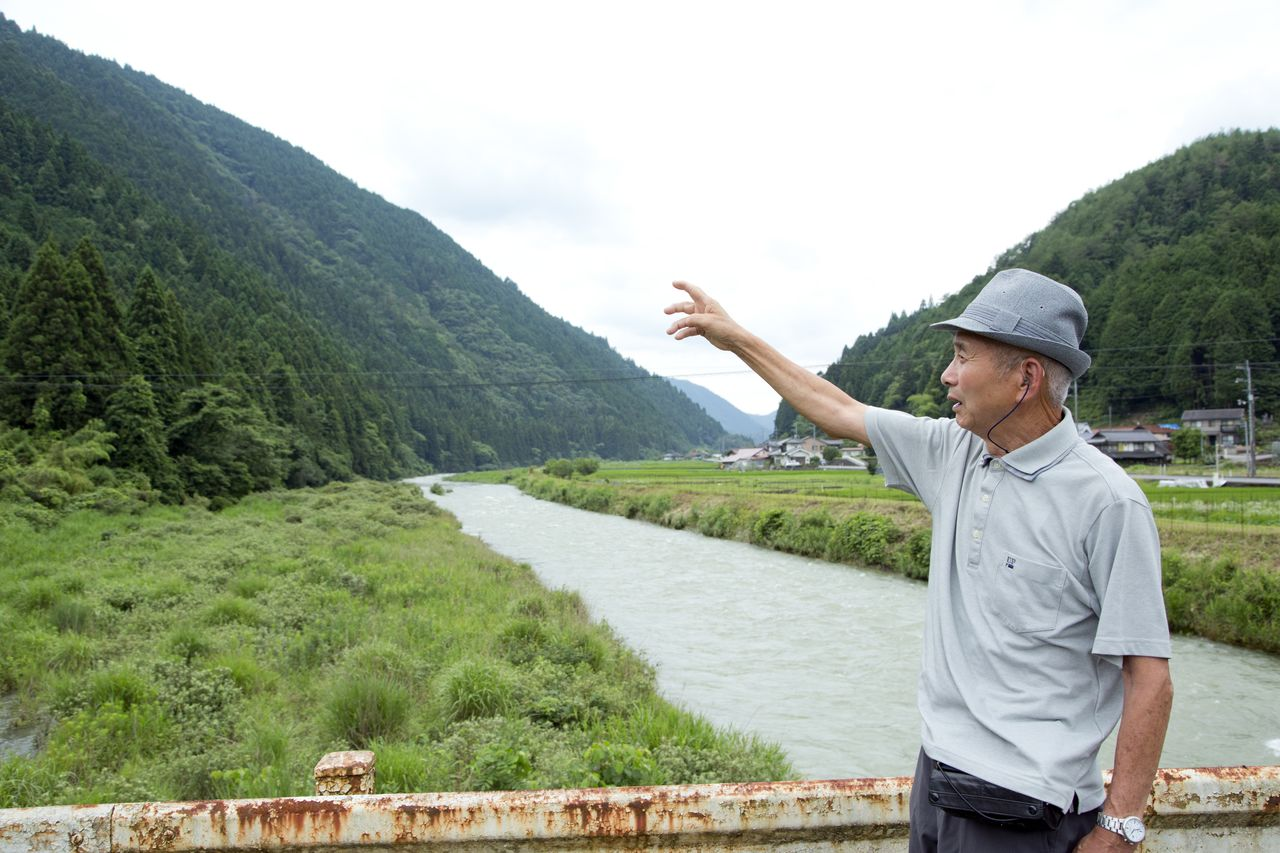 Honke Minoru points to the area south of the Minochi River, whose residents were made eligible for hibakusha healthcare benefits in 1976. Those living on the right bank—including Honke's residence—remained ineligible. (Photo by Dōune Hiroko)