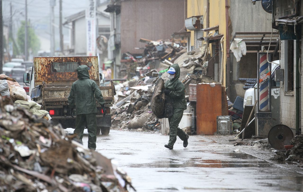 Volunteers cleaning up a residential neighborhood damaged by flooding in Hitoyoshi. (©Jiji)