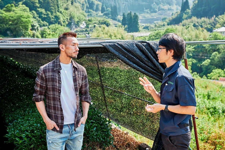 Seorang manajer perkebunan teh, di sebelah kanan, mendiskusikan hasil panennya dengan Nakata. (© Nihonmono)