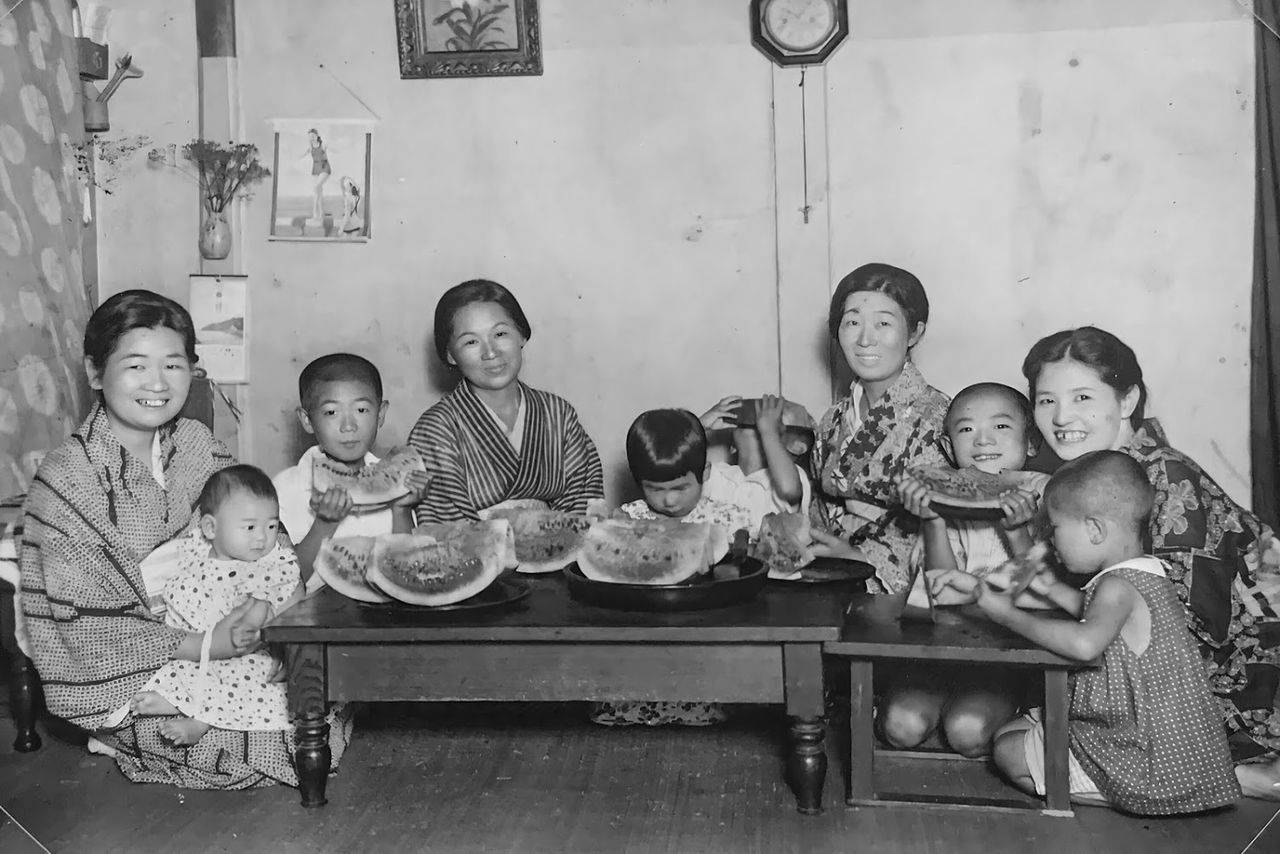 The picture, taken in summer 1936 at the Takahashi photo studio, shows the family enjoying summer watermelon with relatives. The boy covering his face with a watermelon rind is Hisashi. (Courtesy of Takahashi Hisashi)
