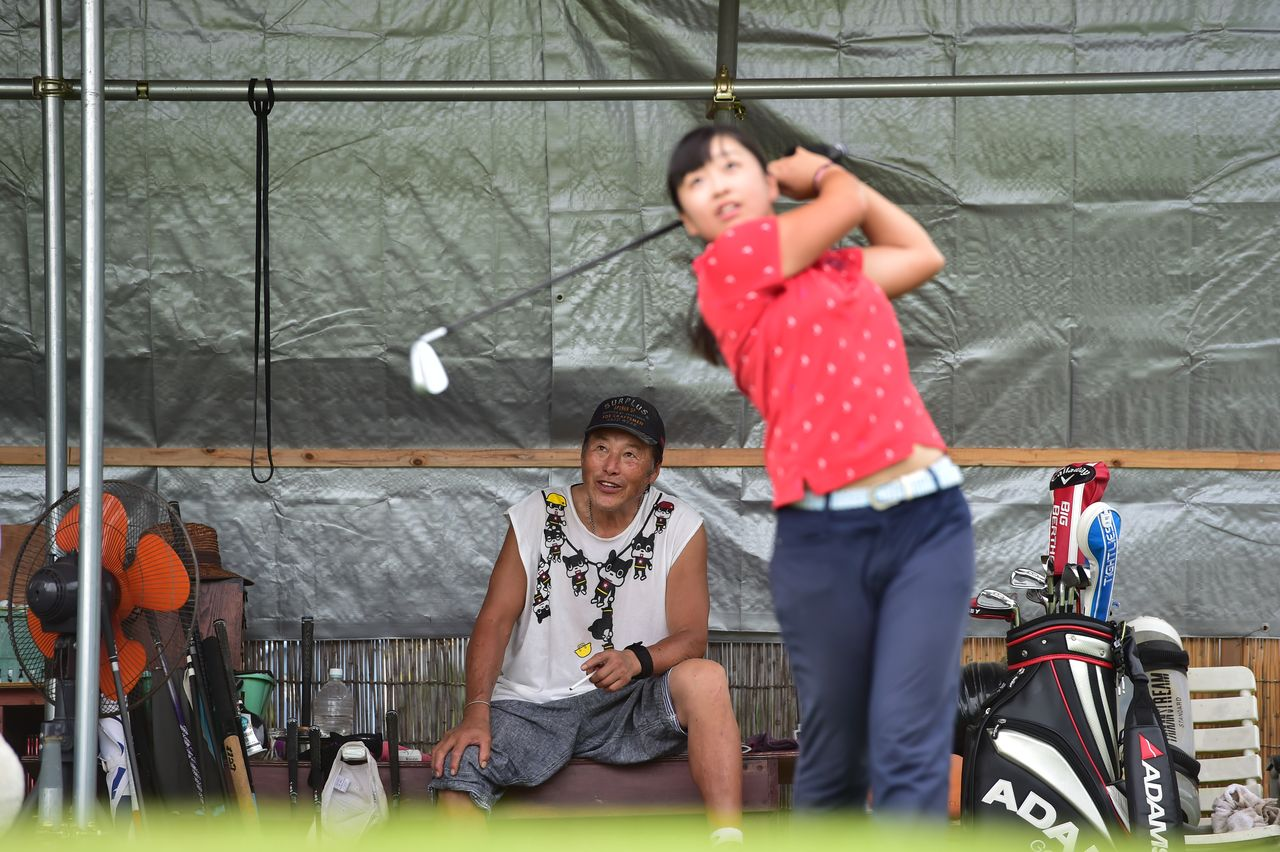 Ozaki Masashi, left, watches Saigō Mao, a high school junior at the time, take practice shots in September 2018. (© Global Golf Media Group)