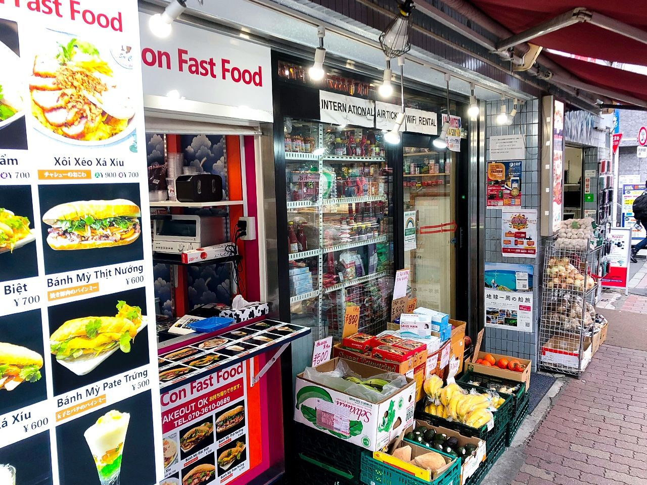 A halal market and a stand selling sandwiches made with banh mi, a type of Vietnamese baguette, share store fronts.
