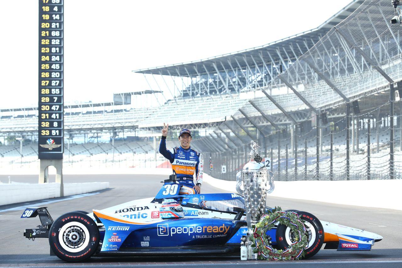 Satō berpose dengan mobilnya di sebelah Borg-Warner Trophy yang diberikan kepada pemenang Indianapolis 500. Piala tersebut memiliki kemiripan dengan pemenang dari 104 balapan yang diadakan hingga saat ini, dan Satō telah menjadi salah satu dari 20 yang tampil di sana lebih dari sekali.