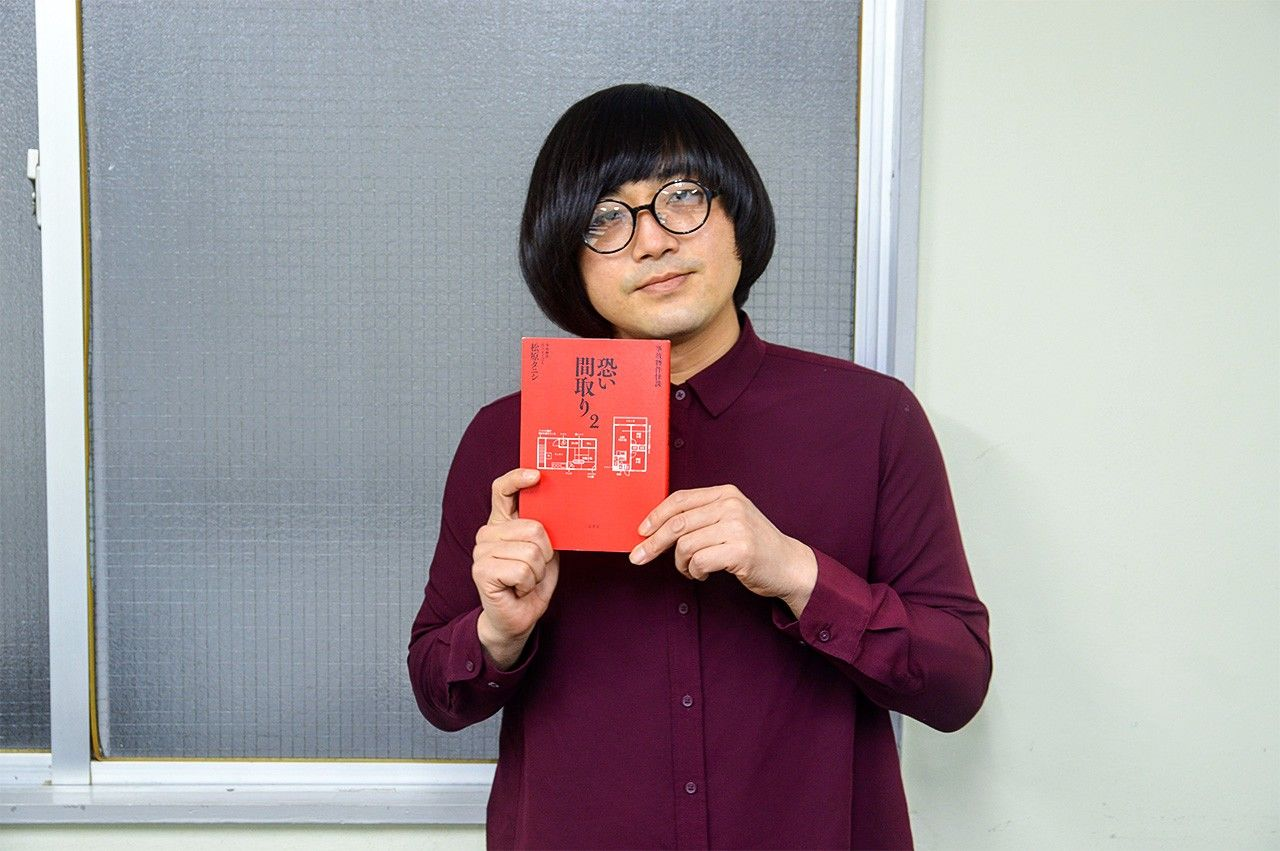 "Matsubara Tanishi with the second volume of his account of living in ""floor plans of fear."" (© Saitō Hayato)"