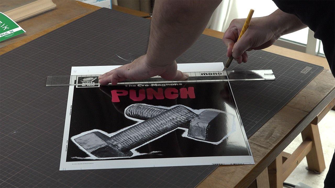 Sugaya mengerjakan sampul album Punch. (© 2020 Epokku no atorie Production Committee)