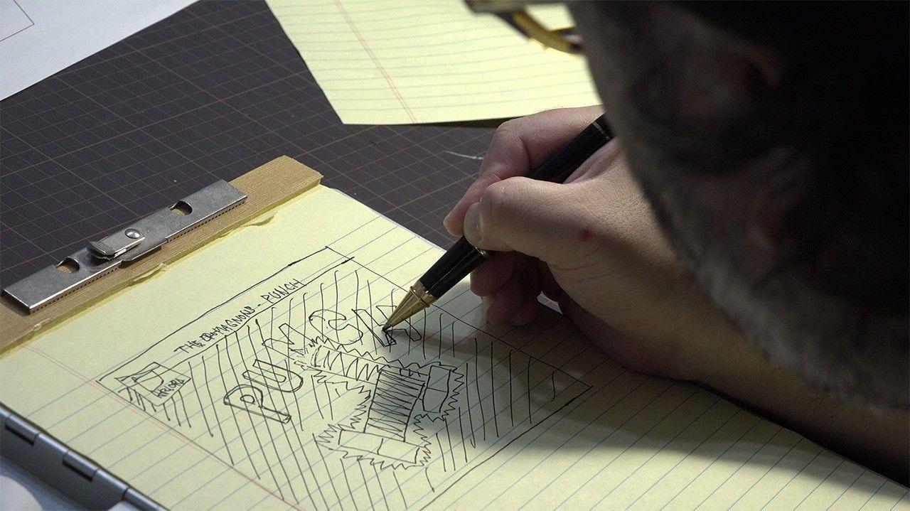 Sugaya membuat sketsa ide di buku catatannya. (© 2020 Epokku no atorie Production Committee.)