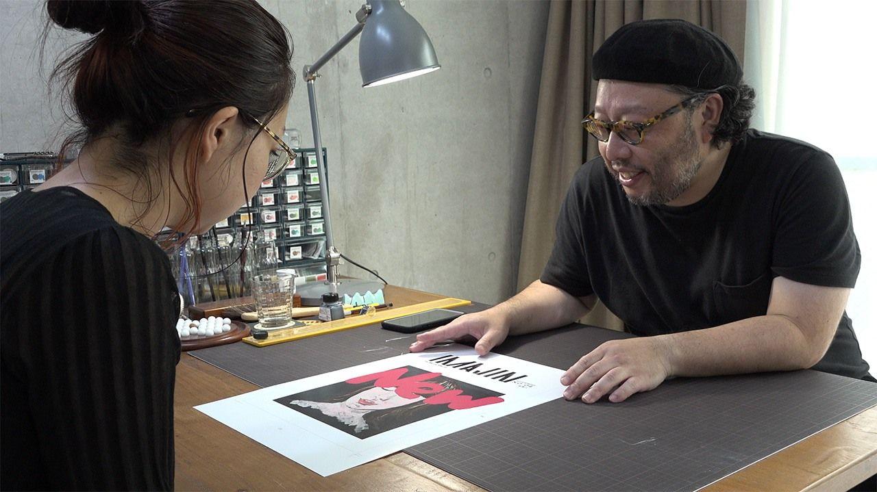 Sugaya menunjukkan karya kepada klien. (© 2020 Epokku no atorie Production Committee)