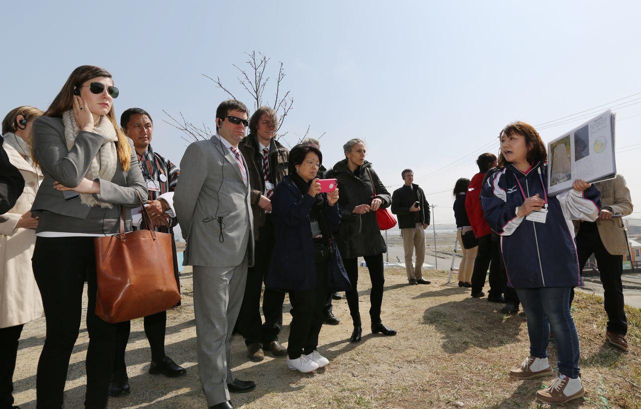 Peserta World Bōsai Forum mengunjungi distrik Yuriage di Natori, Miyagi, pada tanggal 17 Maret 2015, dan mendengarkan penjelasan seorang wanita setempat tentang apa yang dialami para penduduk pada dan setelah 11 Maret 2011. (© Jiji)
