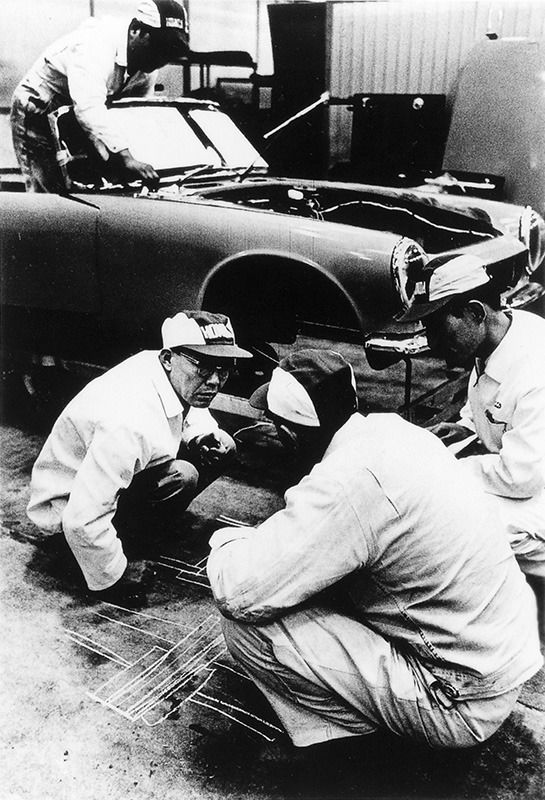 In a 1962 photo taken at the Wakō R&D center, Honda, left, writes diagrams on the floor to explain his ideas to engineers during the development of the S-series sports car.
