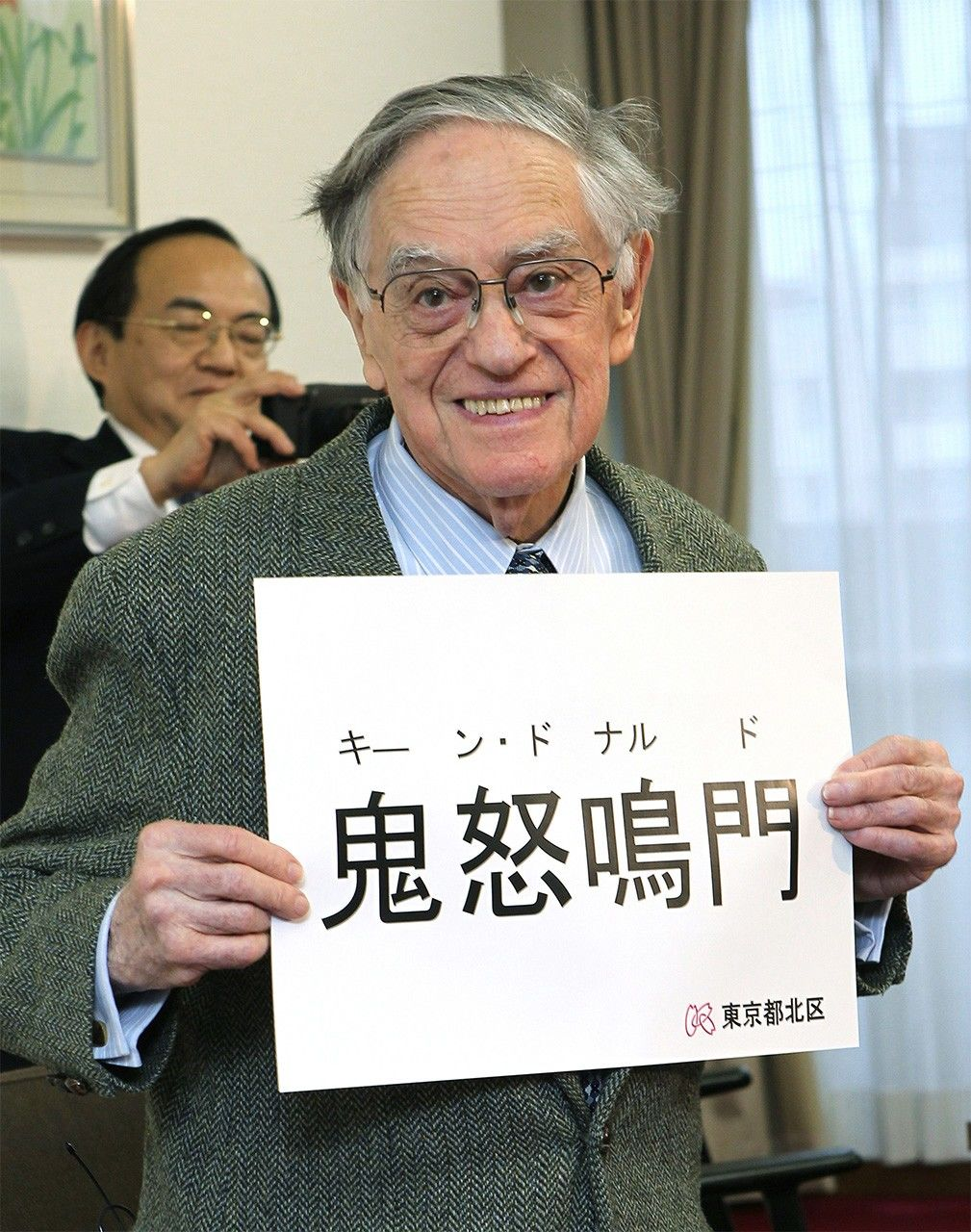 Donald Keene shows reporters his official Japanese name in kanji in Tokyo on March 8, 2012, after taking Japanese citizenship. In the background is his adopted son Seiki. (© Jiji)