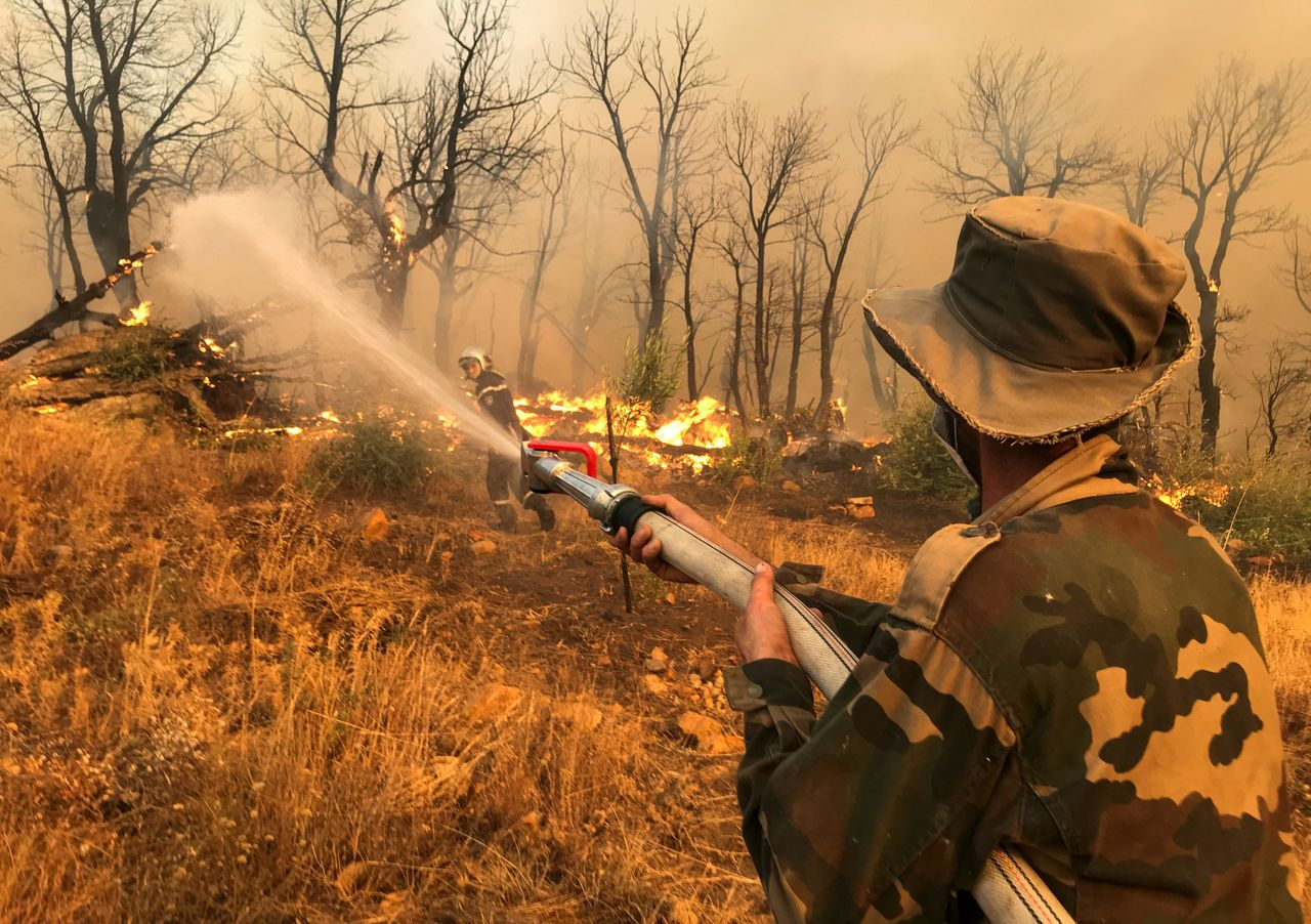 PHOTO DE DOSSIER: Un homme utilise un tuyau d'arrosage pour tenter d'éteindre un incendie dans le village d'Ashlam dans la région montagneuse de Kabylie à Tizi Ouzou, à l'est d'Alger, le 11 août 2021. REUTERS/Abdulaziz Boumzar/File Photo