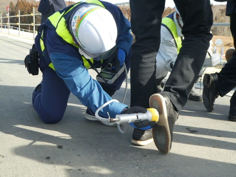 Visitors' shoes are inspected for radiation before they can leave the site.