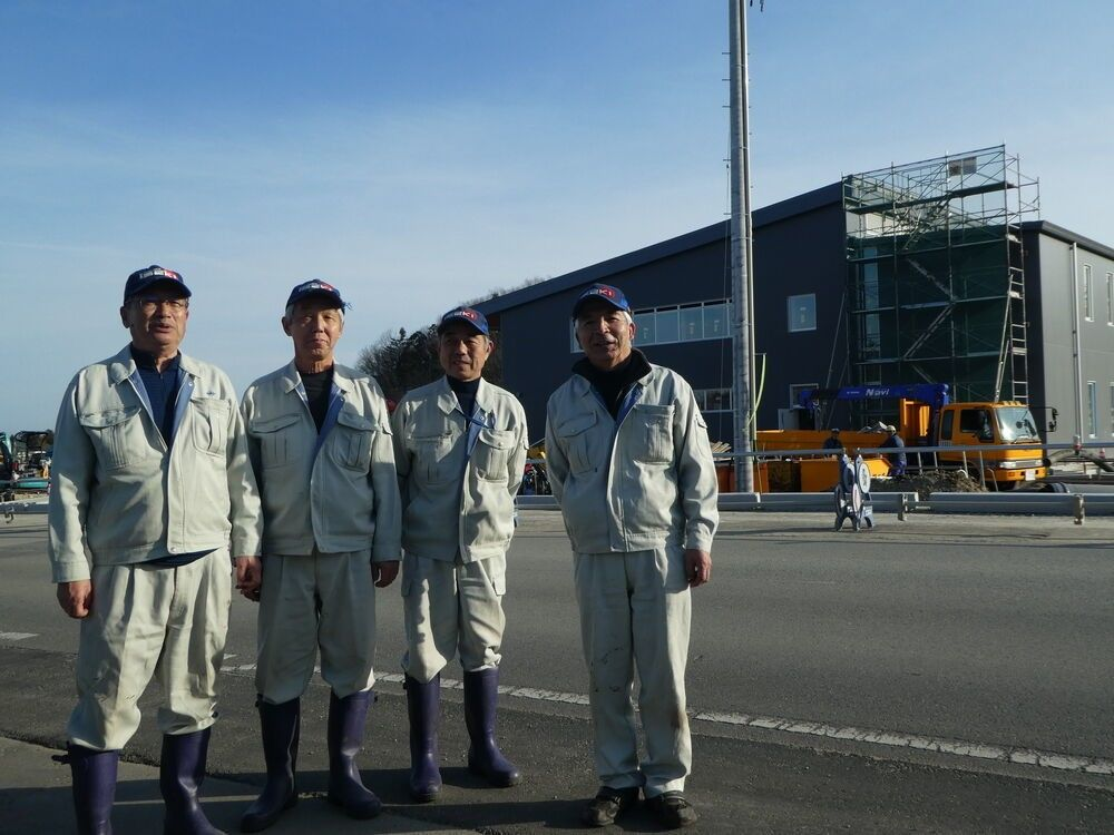 The <em>Jijii-butai</em> (Old Men's Battalion), a group of retired town office employees, worked for years to maintain the ghost town that was Ōkuma in the belief that one day people would return. In March, their job will be over. The new town office is visible in the background.