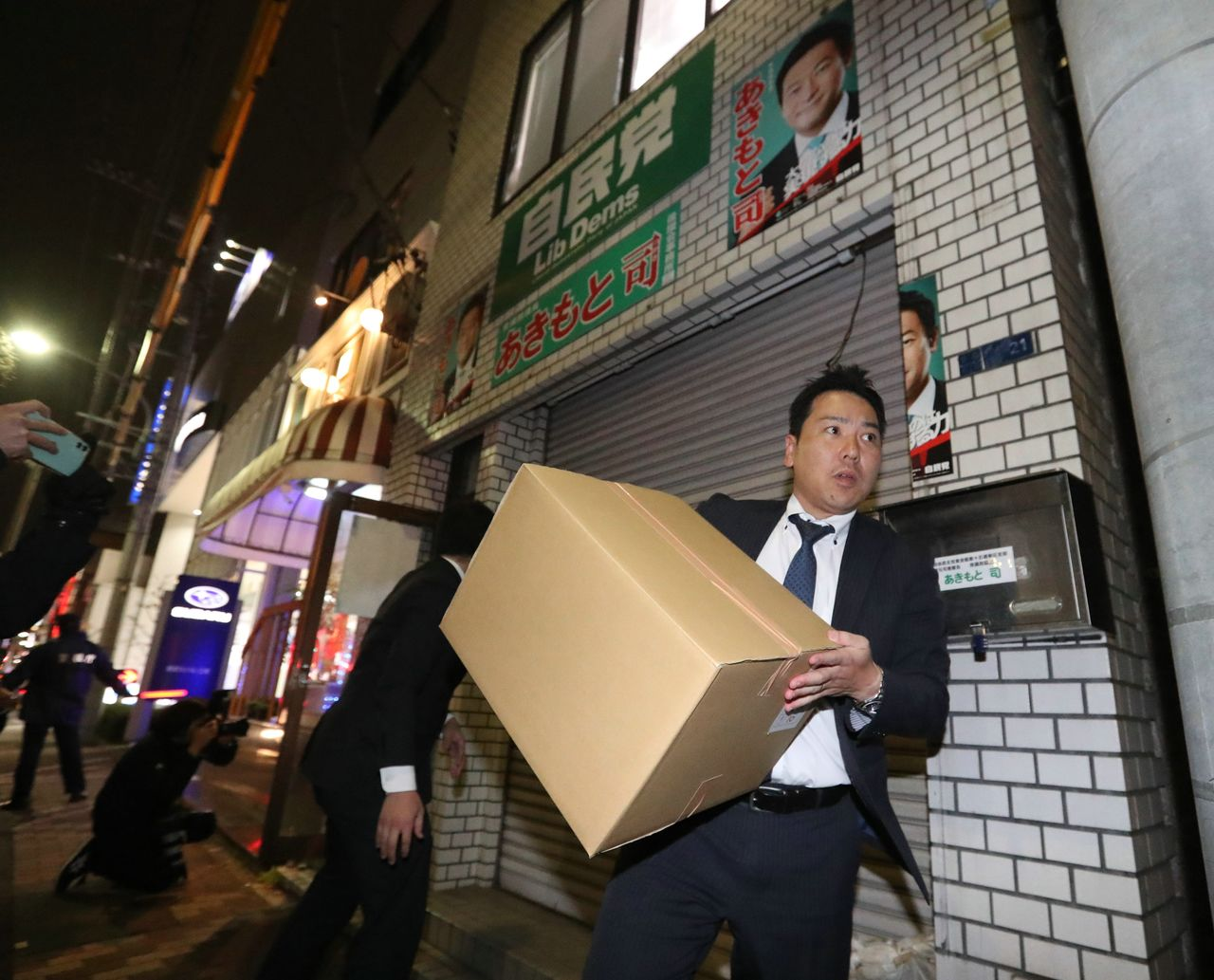An official from the Tokyo District Public Prosecutors Office carries a box containing confiscated items from the office of House of Representatives member Akimoto Tsukasa in Kōtō ward, Tokyo, on December 19, 2019. (© Jiji)