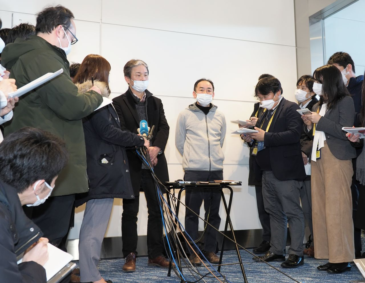 Japanese citizens flown home from Wuhan talk to members of the press at Haneda Airport on January 29, 2020. (© Jiji)