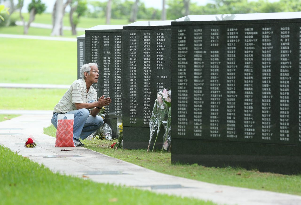 A man prays in front of the Cornerstone of Peace monument in the Peace Memorial Park in Itoman, Okinawa, on June 23, 2020. (© Jiji)