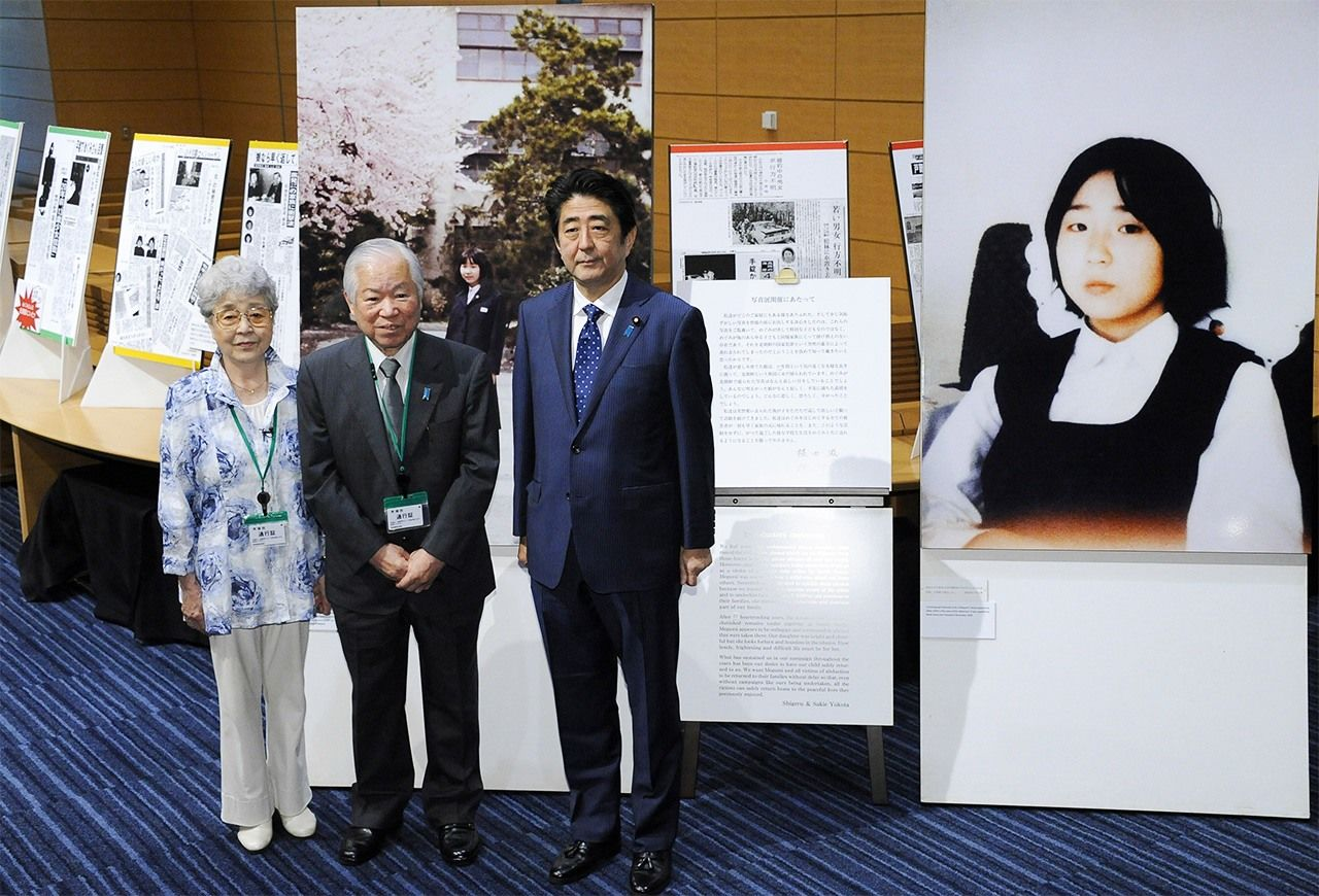 Prime Minister Abe Shinzō (right) with Yokota Shigeru (center) and his wife Yokota Sakie in Tokyo on June 10, 2014. The panel to the right shows Yokota Megumi, who was abducted by North Korea at the age of 13. (© Jiji)